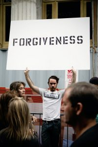 man holding up sign that says forgiveness