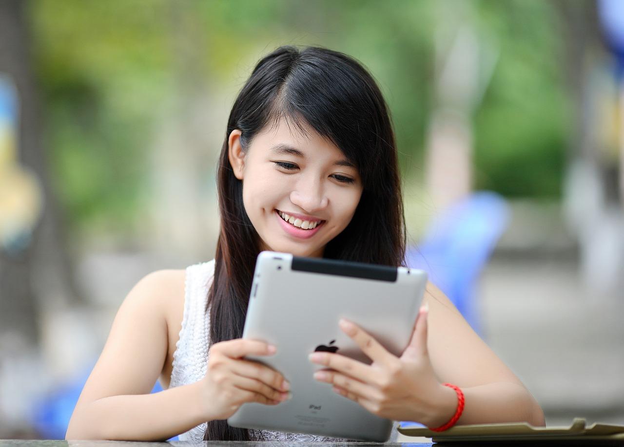 Asian teen girl using iPad